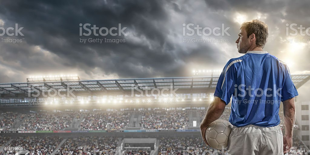 male soccer player standing in front of a large crowd stock photo