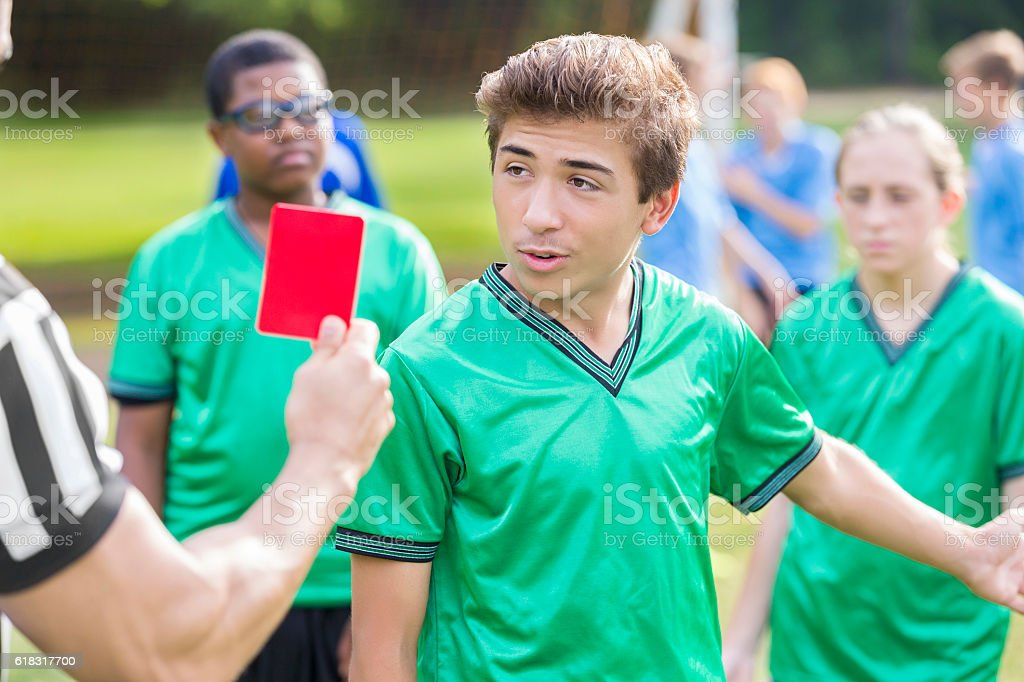 Male soccer player talks with referee about penalty call stock photo