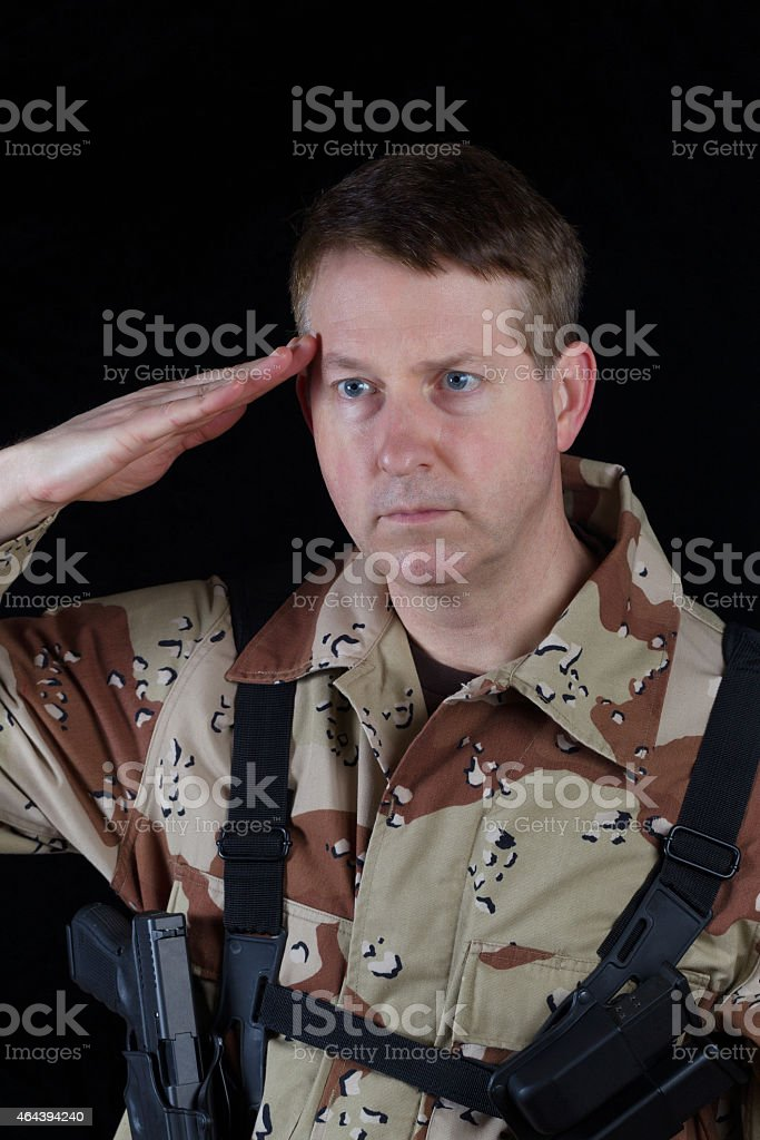 Male Soldier saluting while under arms stock photo