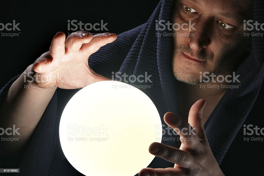Male sorcerer looking in crystal ball stock photo