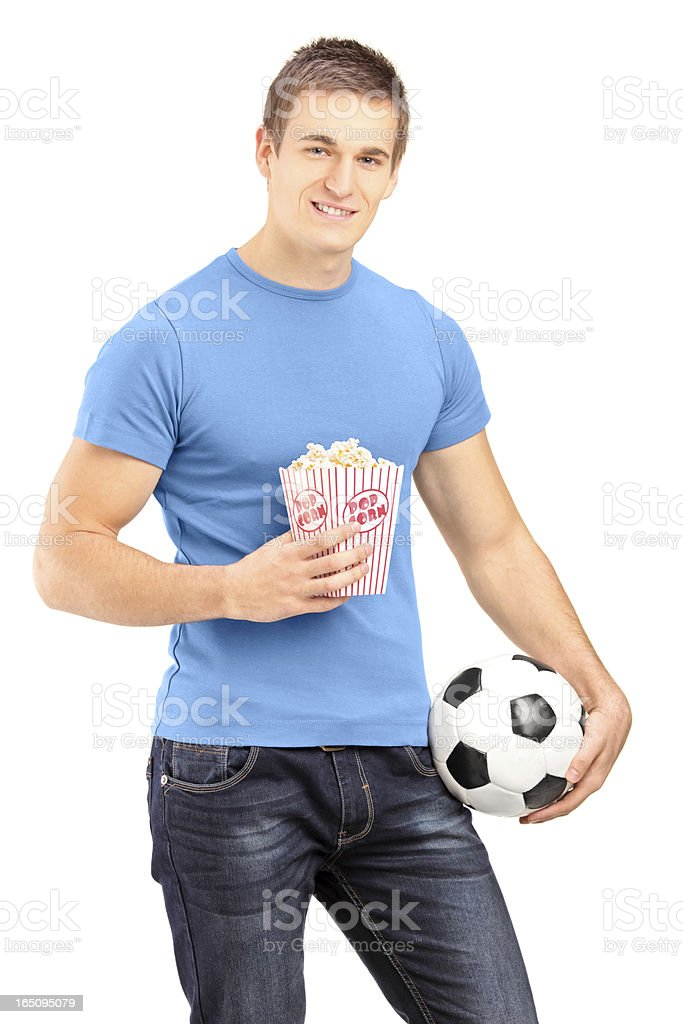 Male sports fan holding a football and popcorn box royalty-free stock photo