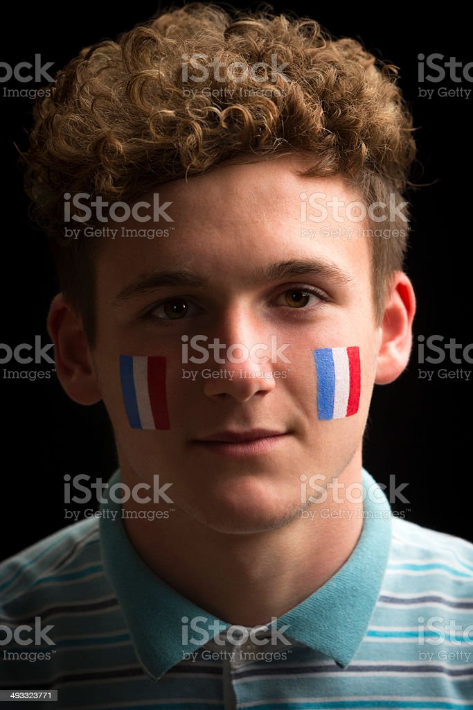Male sports fan with French flag painted on face.