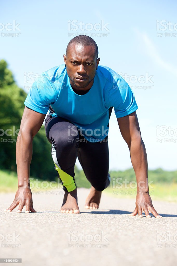 Male sports man in starting position for a race stock photo