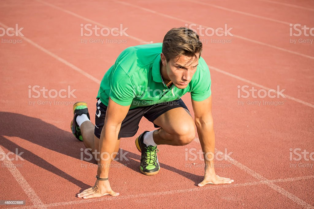 Male sprinter in clothes at start position, on red track. stock photo