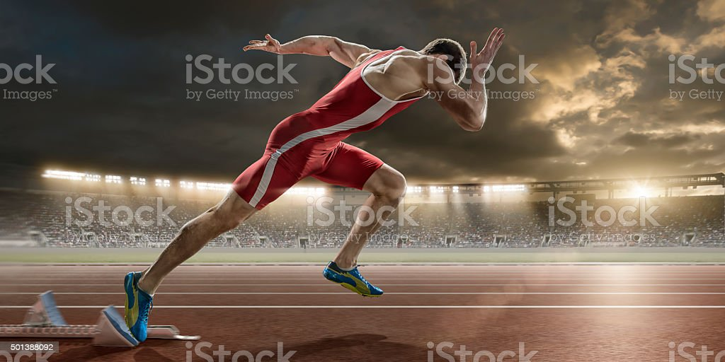 Male Sprinter Sprint Starts From Blocks in Athletics Stadium stock photo