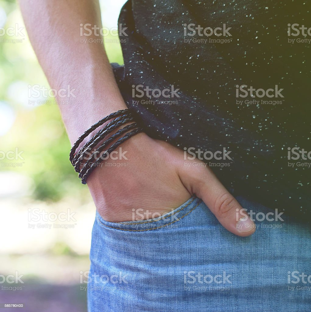 Male standing with leather bracelet on his hand stock photo