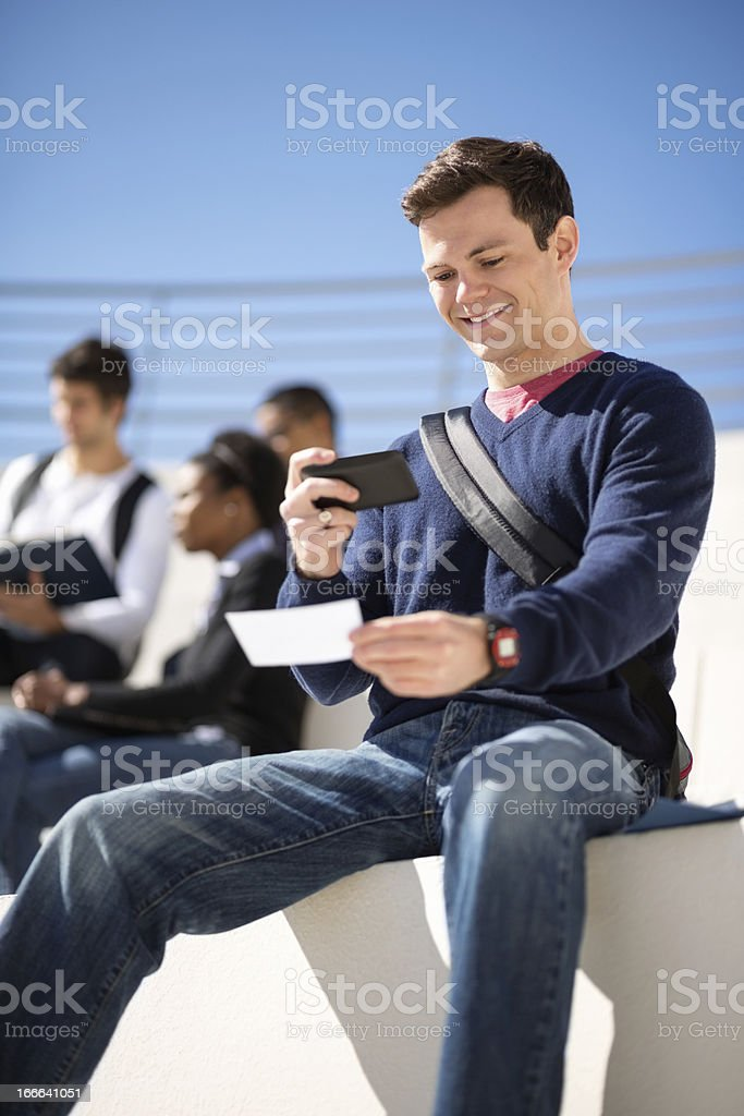 Male Student Depositing Check Through Smart Phone stock photo