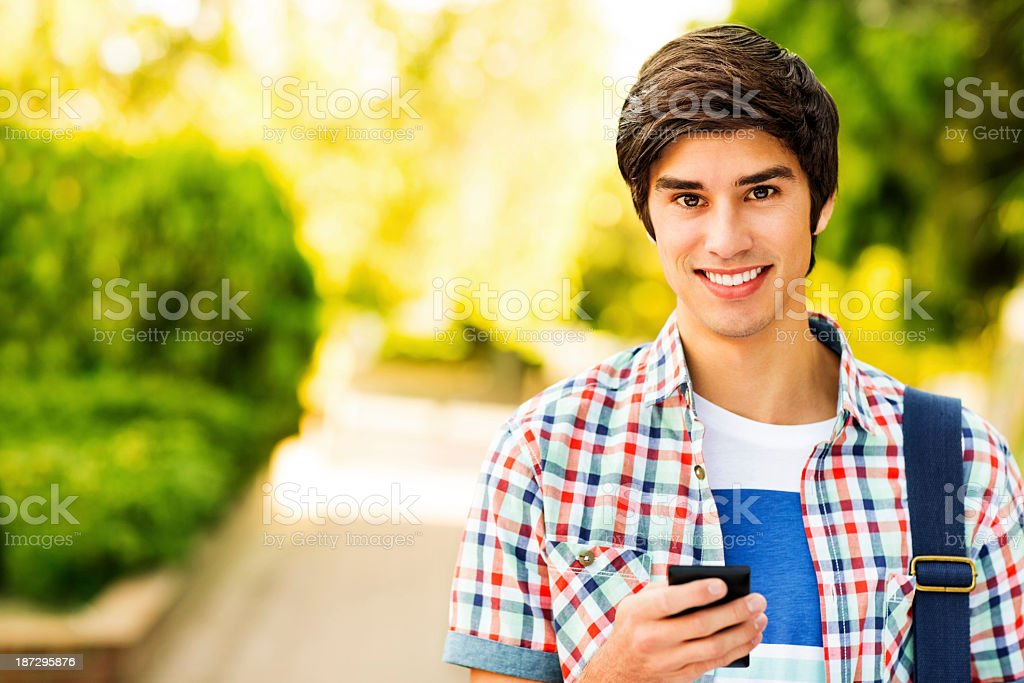 Male Student Holding Smart Phone On College Campus royalty-free stock photo