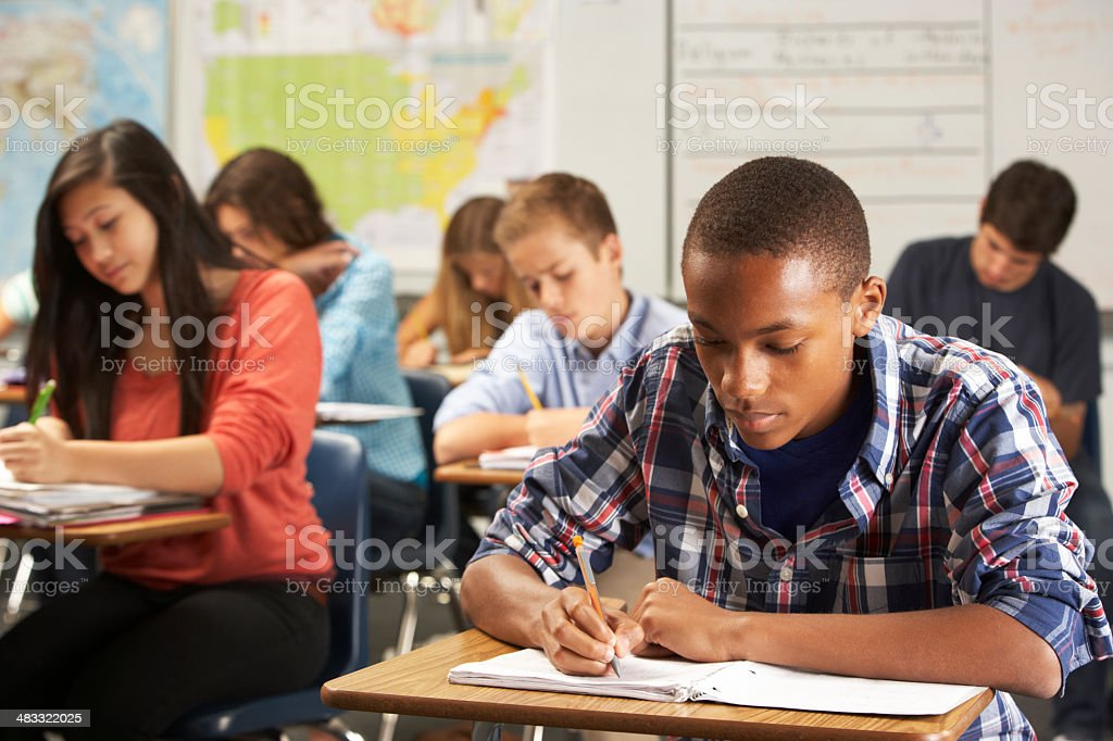 Male student in classroom writing in notebook stock photo