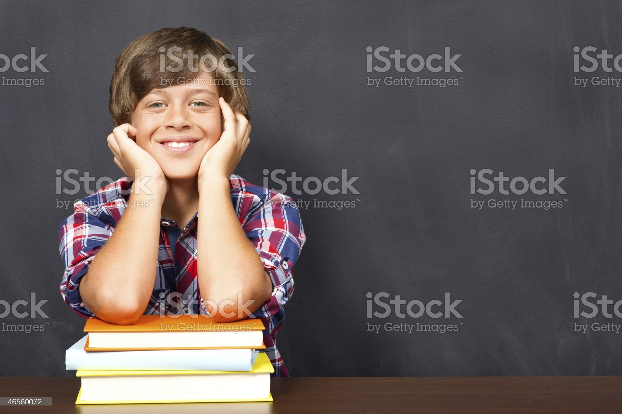 A male student resting his elbows on a stack of books royalty-free stock photo