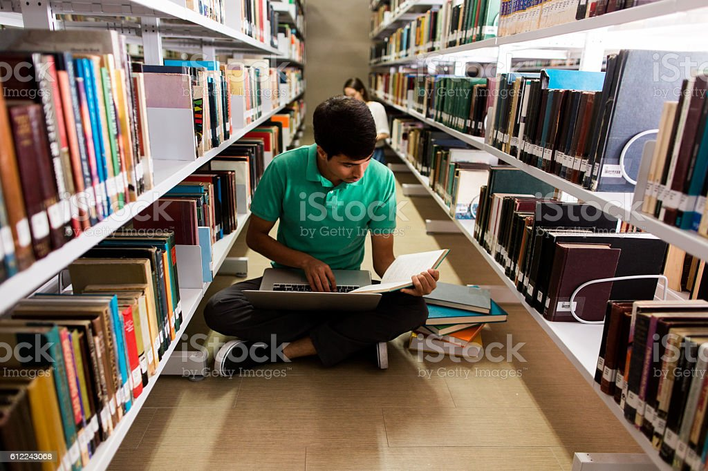 Male student sitting on the floor with books and computer stock photo
