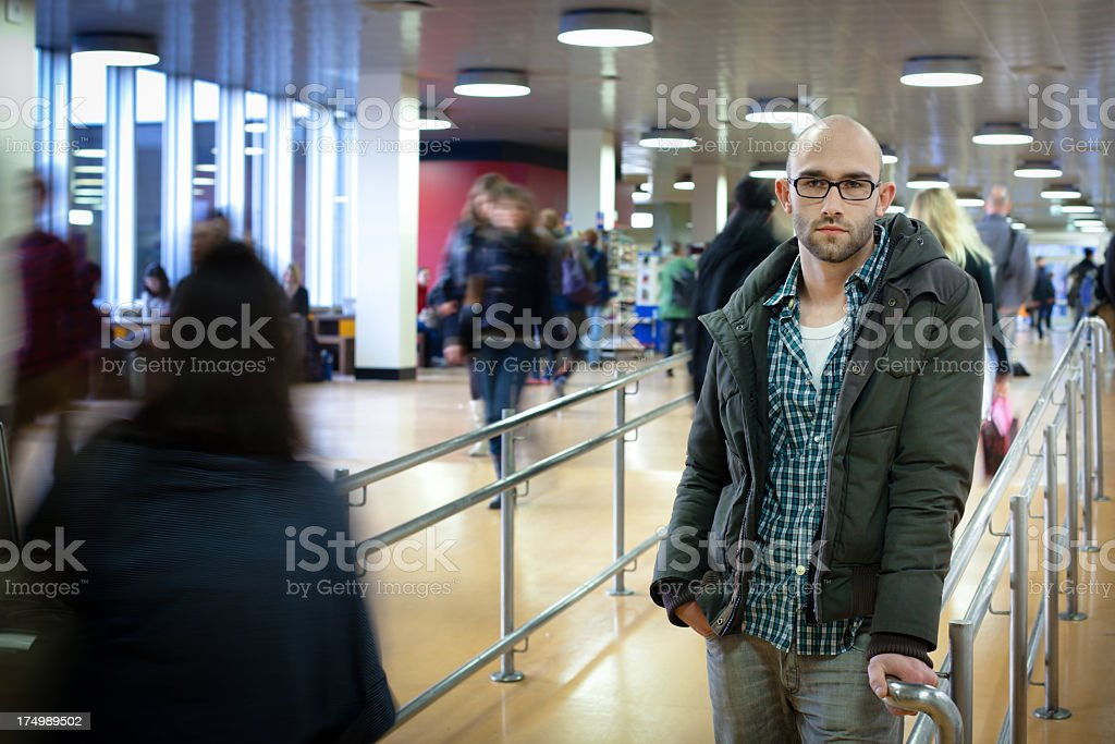 male student stands in corridor between motion blurred crowd royalty-free stock photo