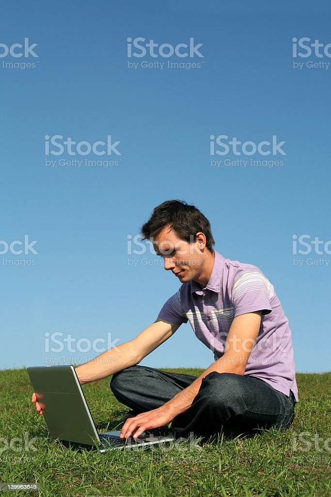 Male student using a laptop computer outdoors royalty-free stock photo