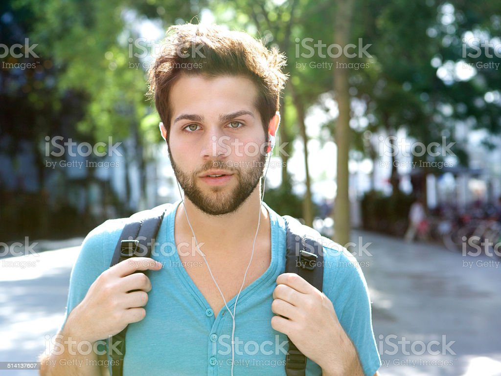 Male student walking outdoors with bag stock photo