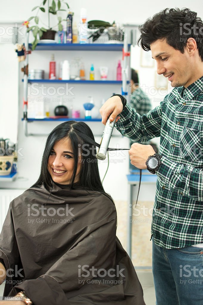 Male stylist using hair straightener on woman's hair at salon. stock photo