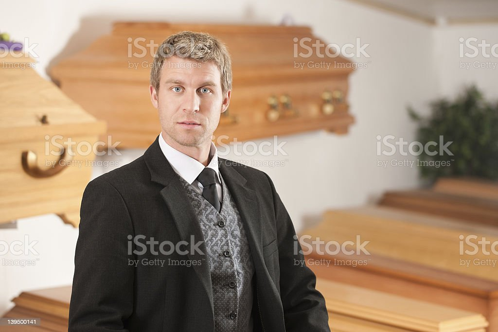 Male suited undertaker with coffins in background stock photo