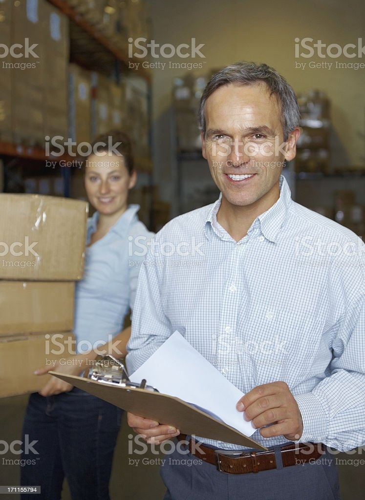 Male supervisor smiling at warehouse with female worker in background royalty-free stock photo