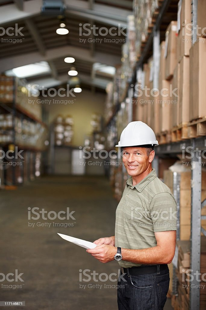 Male supervisor with report standing at the warehouse royalty-free stock photo
