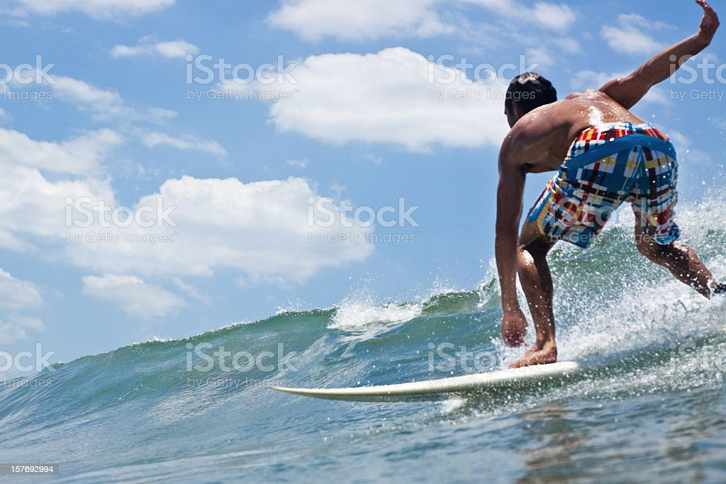 A male surfer bending down to ride a wave stock photo