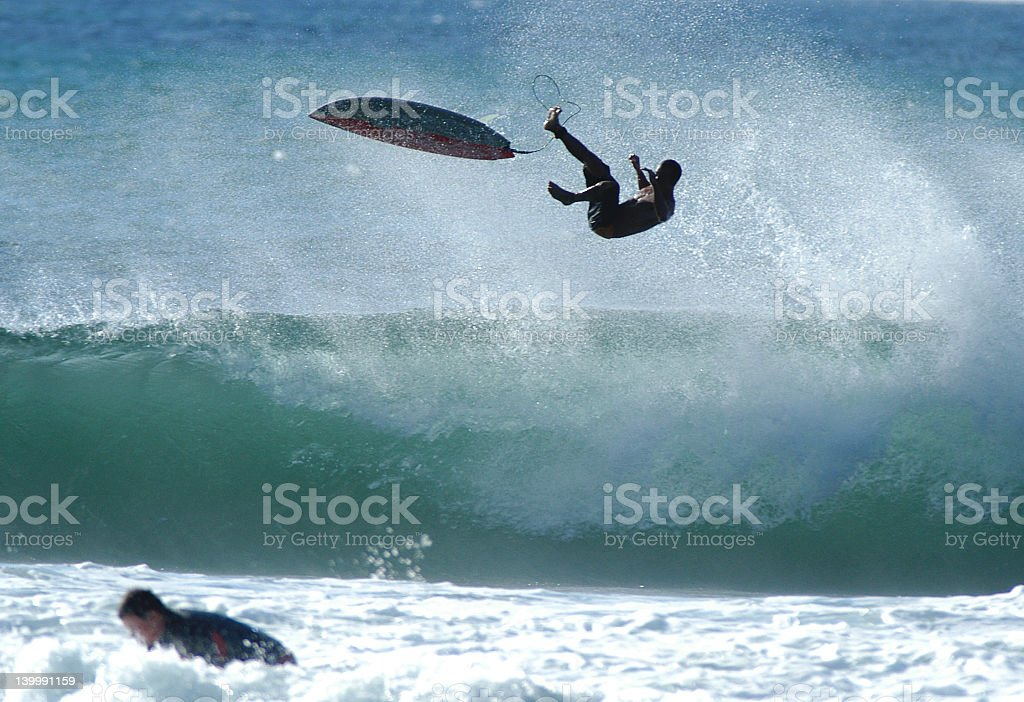 A male surfer falling off his surfboard stock photo