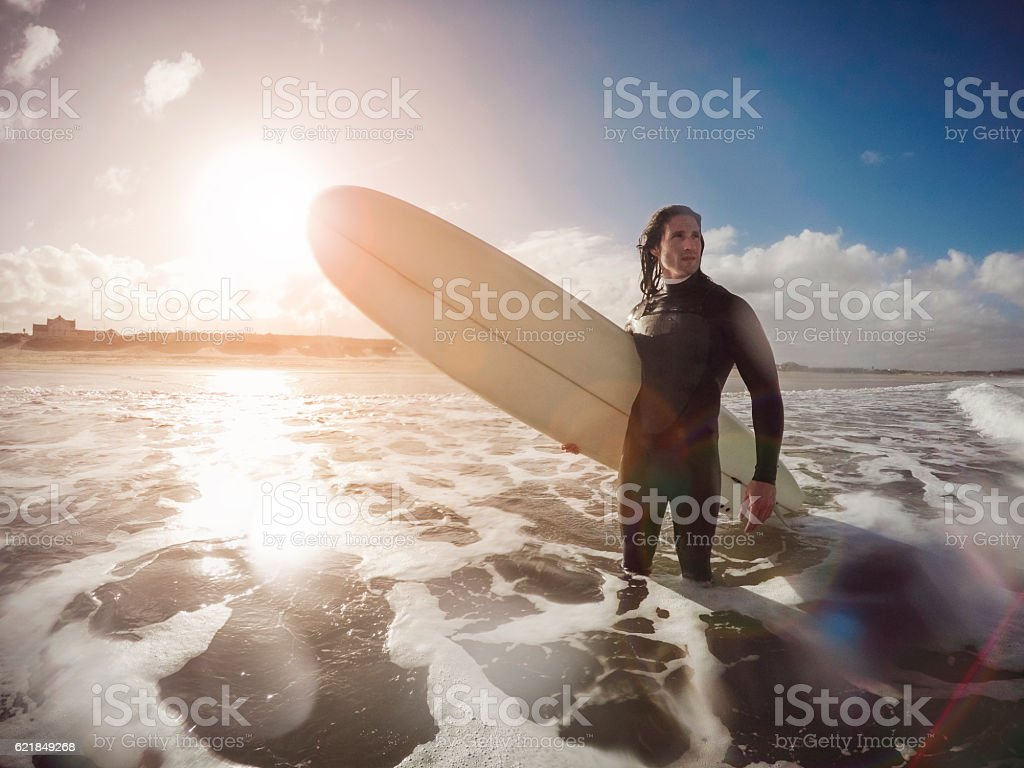 Male Surfer Standing in the Sea stock photo