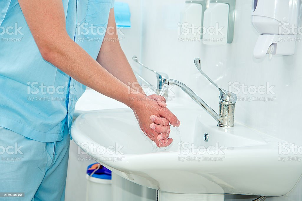 Male surgeon washes his hands stock photo