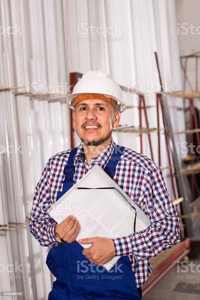 Male surveyor in coverall doing checkup and filling papers stock photo