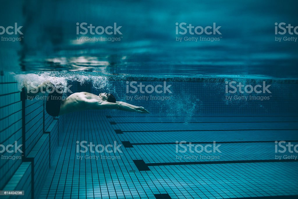 Male swimmer turning over in swimming pool stock photo