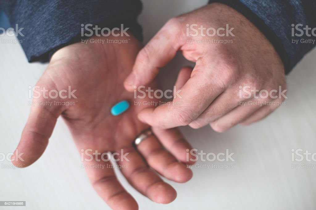Male taking blue pills from hands close up stock photo