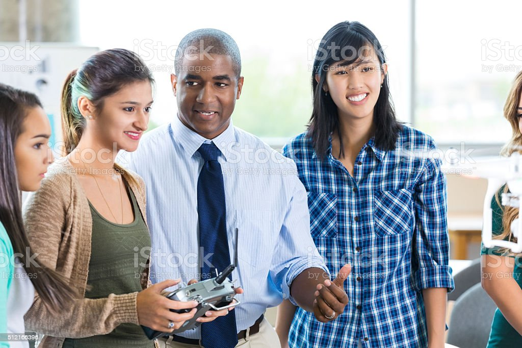 Male teacher advises student in STEM school stock photo
