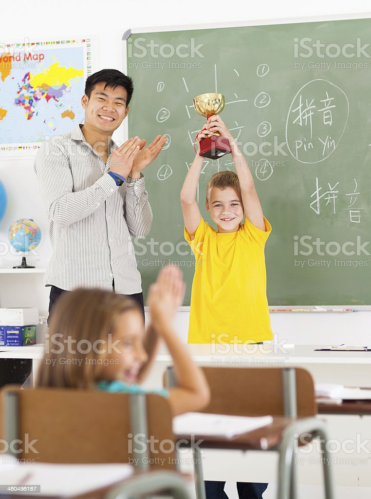 male teacher applauding for student stock photo