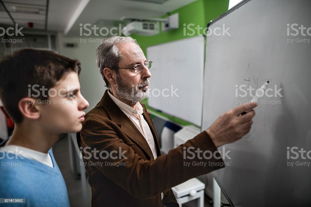 Male teacher explaining a lesson to high school student. stock photo