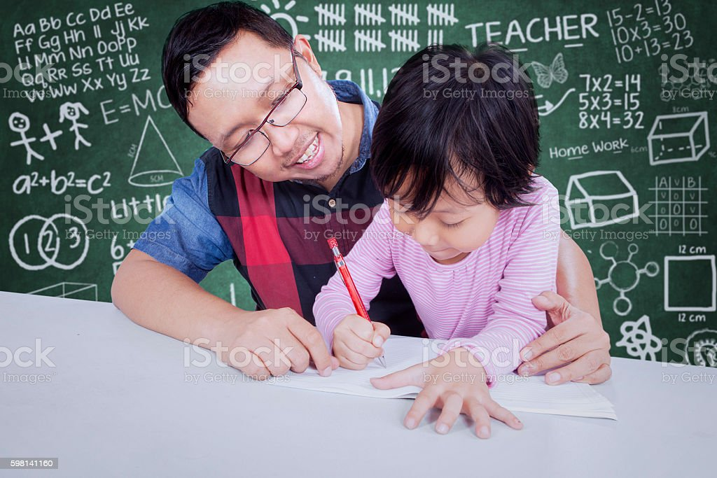 Male teacher guide a student to write stock photo