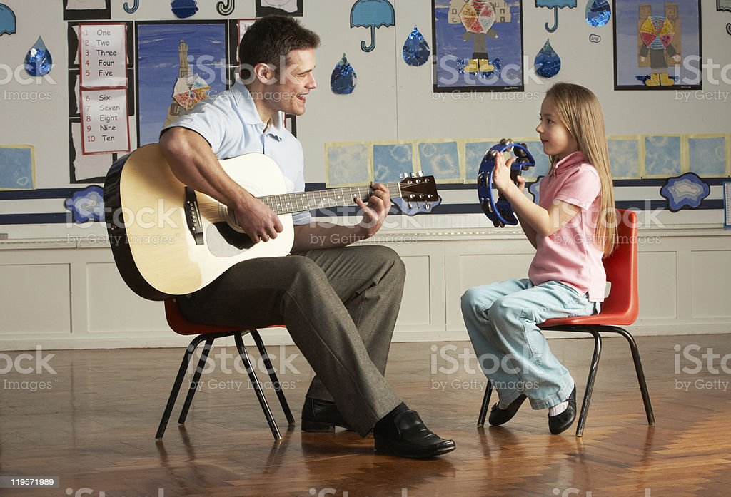Male Teacher Playing Guitar With Pupil In Classroom stock photo