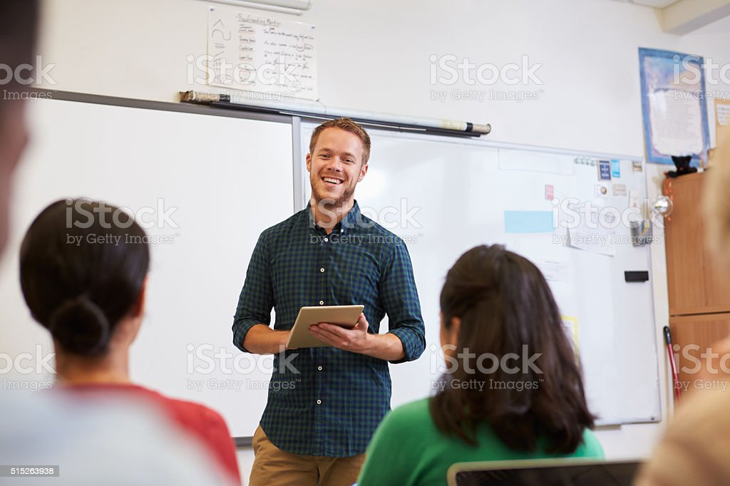 Male teacher using tablet computer at adult education class stock photo