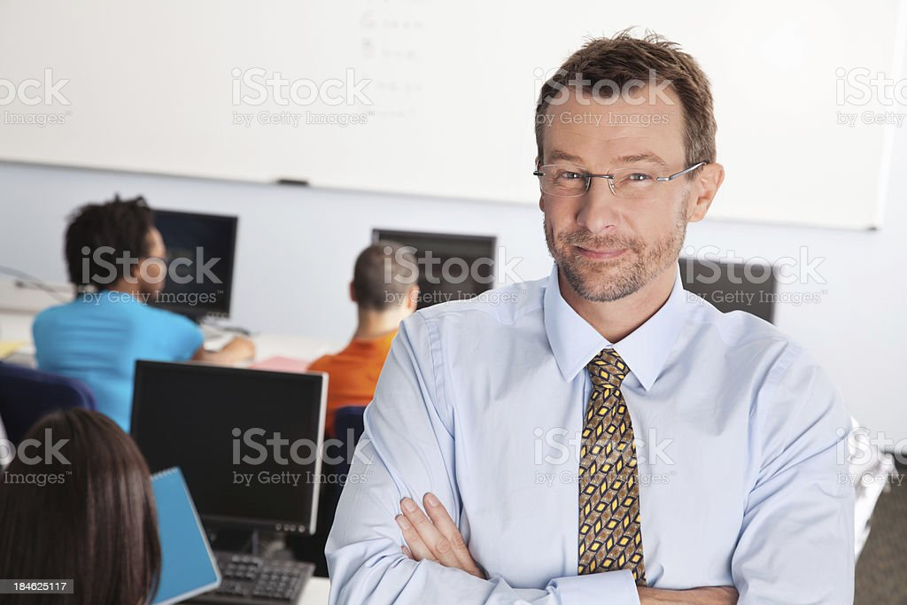 Male Teacher With Arms Crossed in His Classroom royalty-free stock photo
