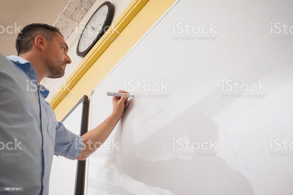 Male teacher writing on whiteboard in classroom stock photo