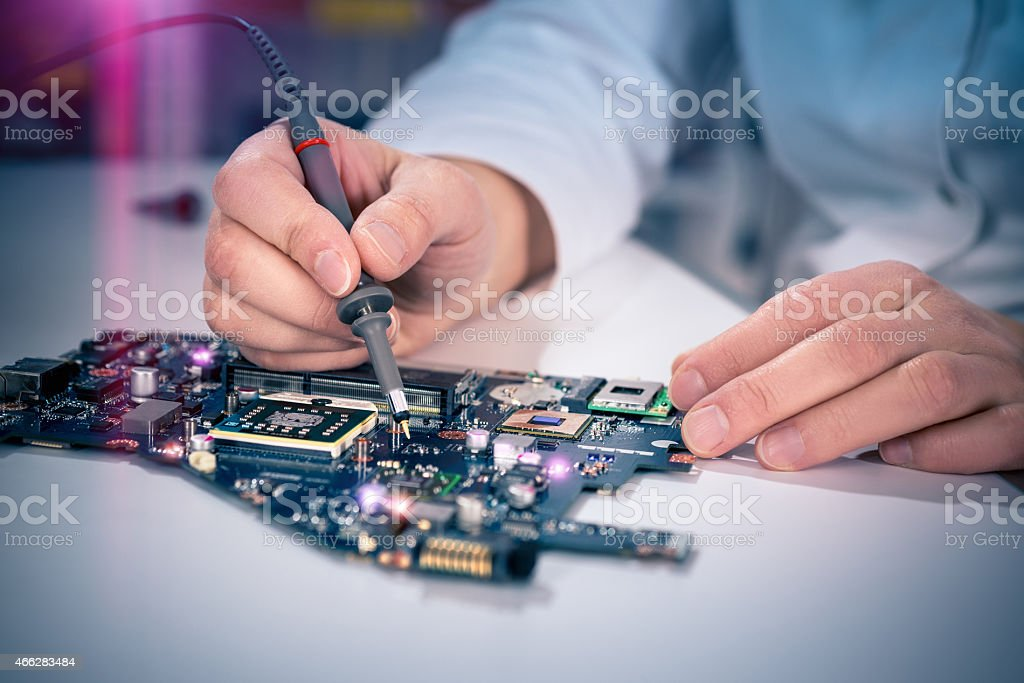 A male tech worker tests an electronic circuit board stock photo