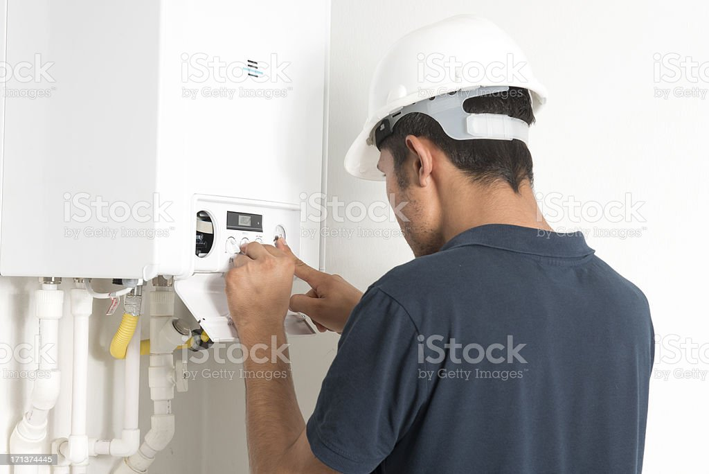 Male technician working in a boiler in a white room royalty-free stock photo