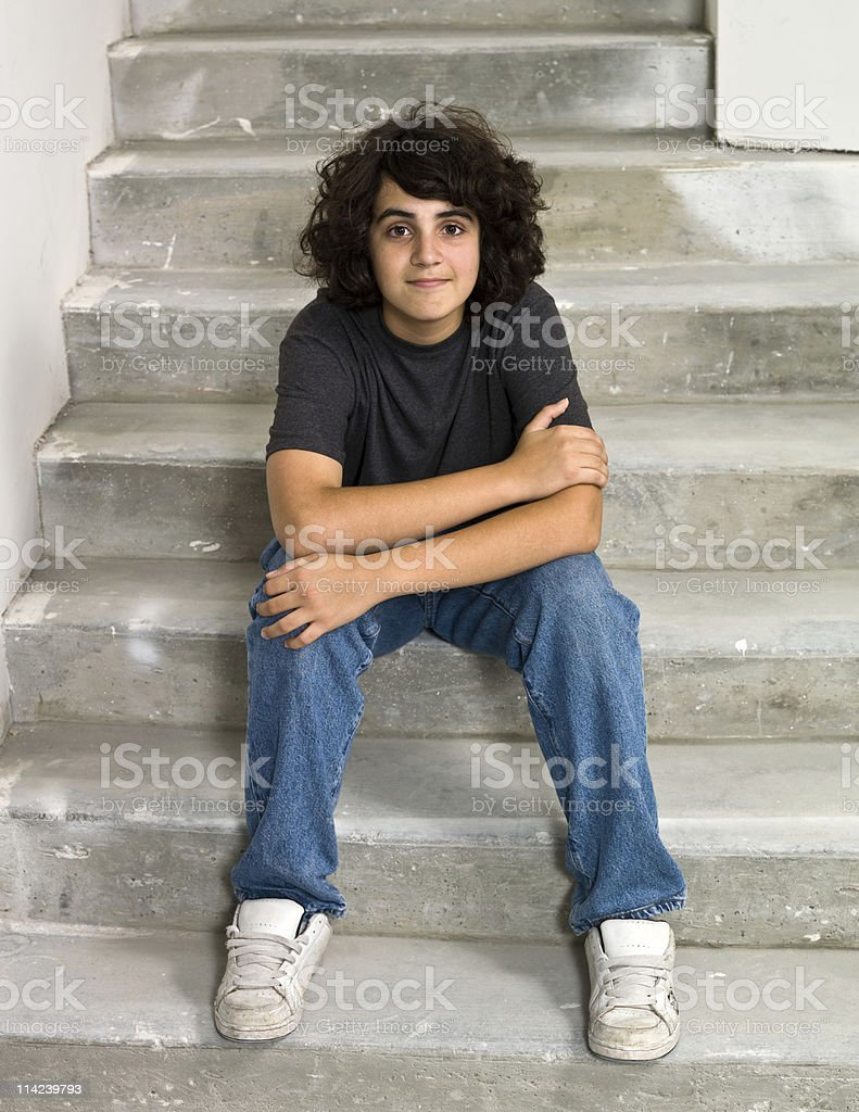 Male Teen sitting on the stairs stock photo