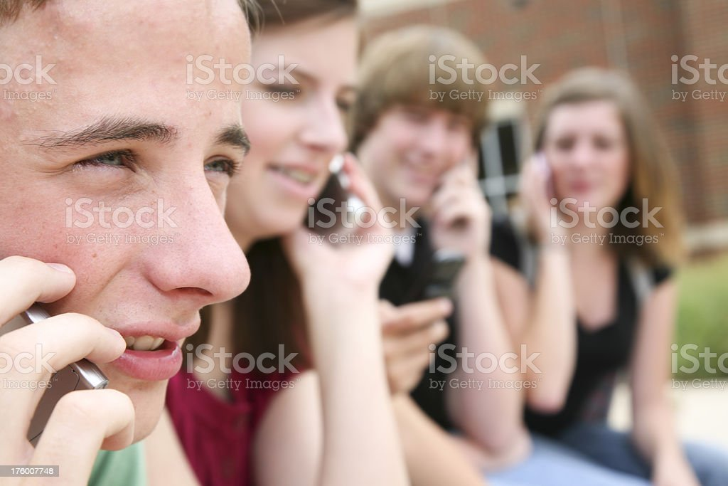 Male Teenager and His Friends on Their Cell Phones royalty-free stock photo