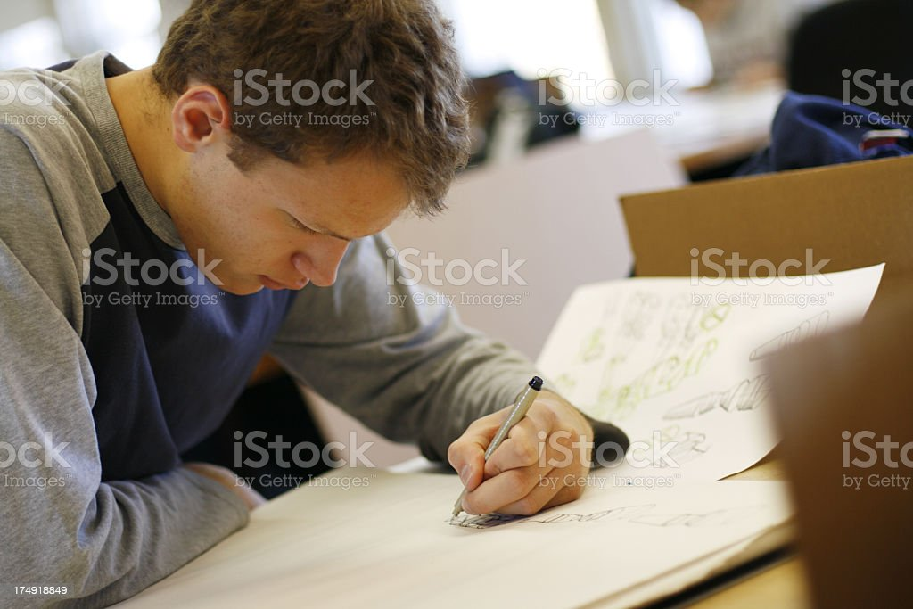 A male teenager drawing on paper royalty-free stock photo
