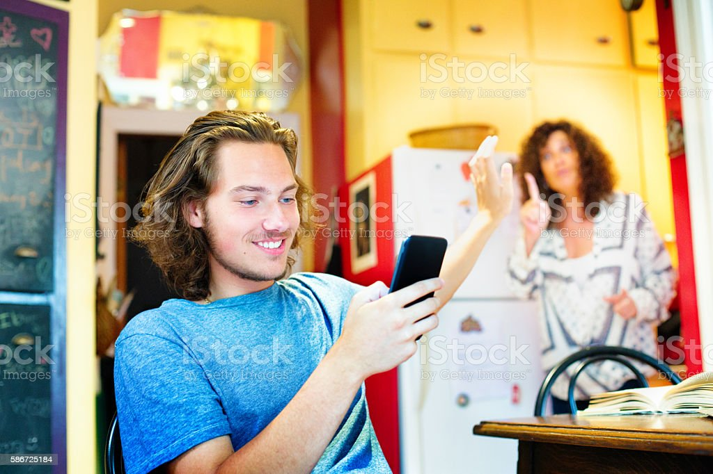 Male teenager gestures mom to wait while using mobile phone stock photo