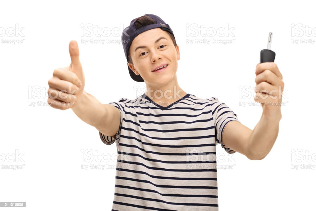 Male teenager making thumb up gesture and holding car key stock photo