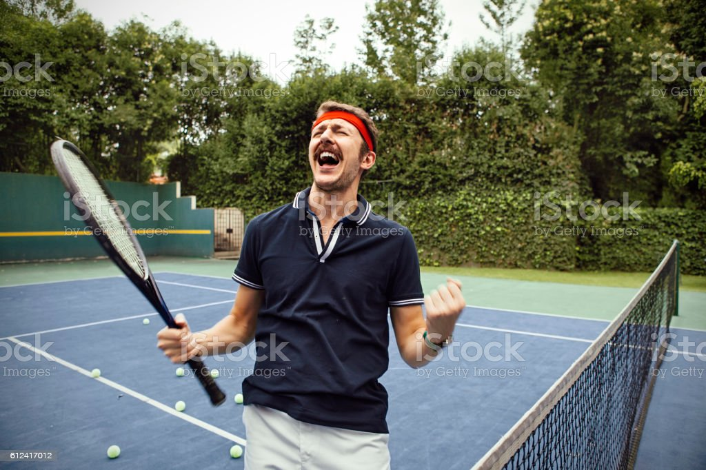 Male tennis player celebrating win stock photo
