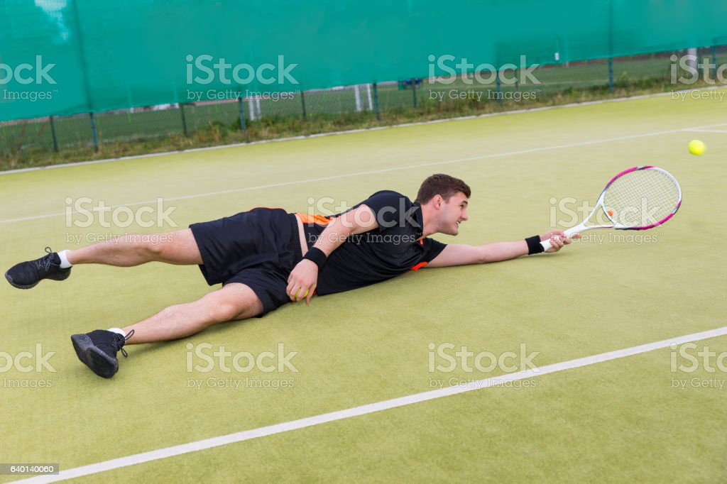 Male tennis player in action during the game fallen stock photo