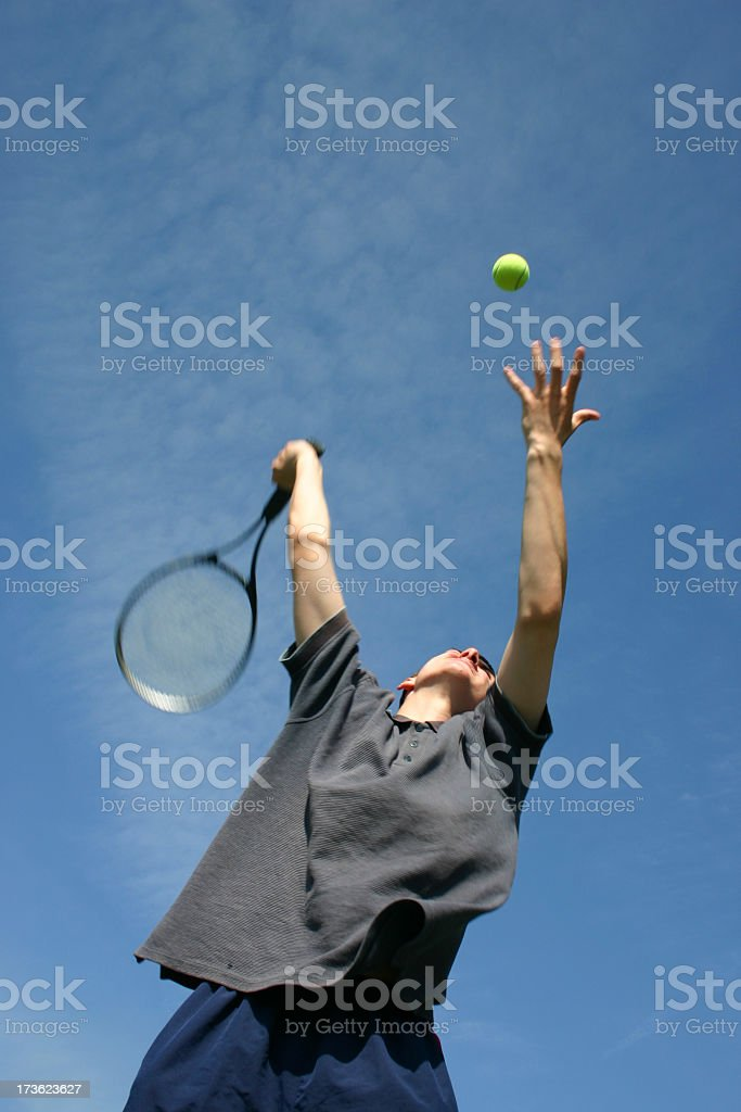 Male tennis player jumping and serving royalty-free stock photo