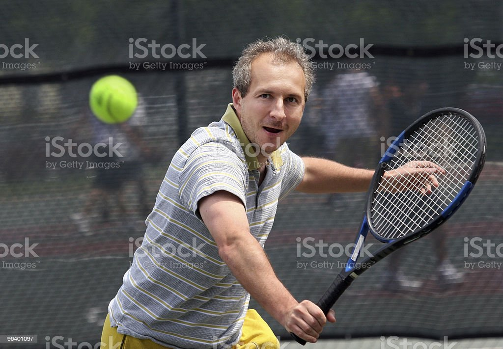 A male tennis player taking a shot stock photo