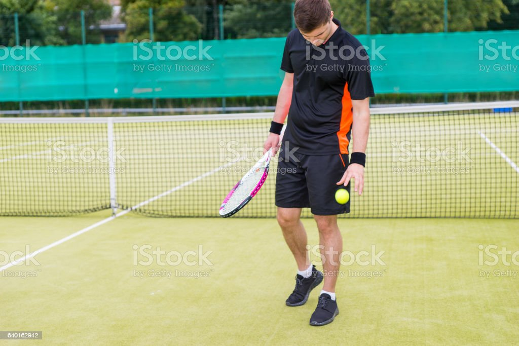 Male tennis player throws the ball after a match stock photo
