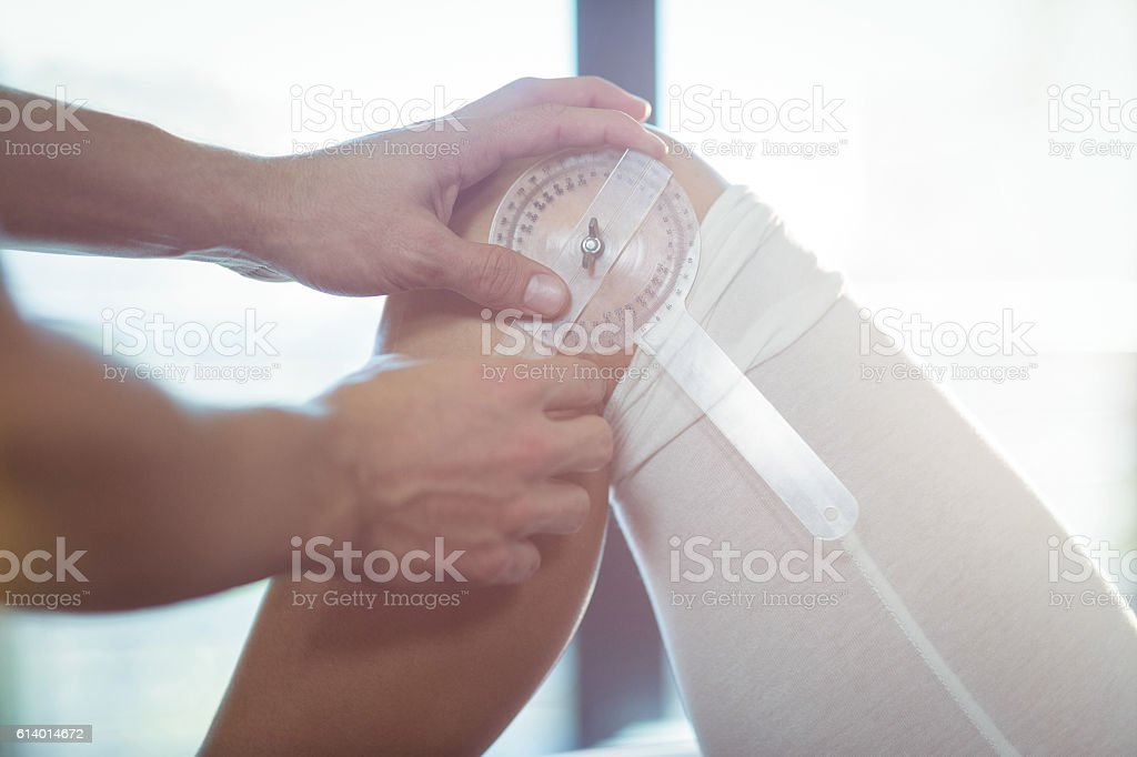 Male therapist measuring female patient knee with medical ruler stock photo